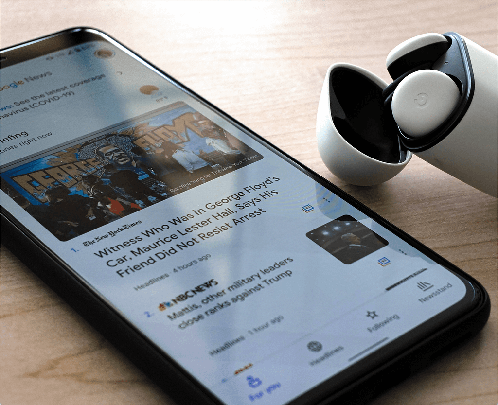 smart phone on a table portraying a news feed with a sed of airpods in its container next to it