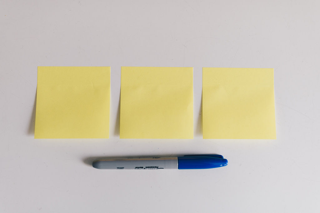 three yellow post-it notes in a row on a white background with a blue-capped sharpie lying beneath it