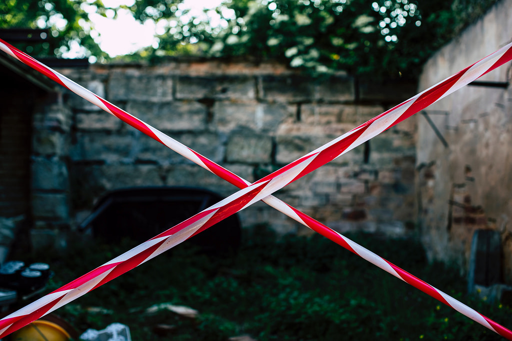 Red and white police tape in a criss cross in front of a site