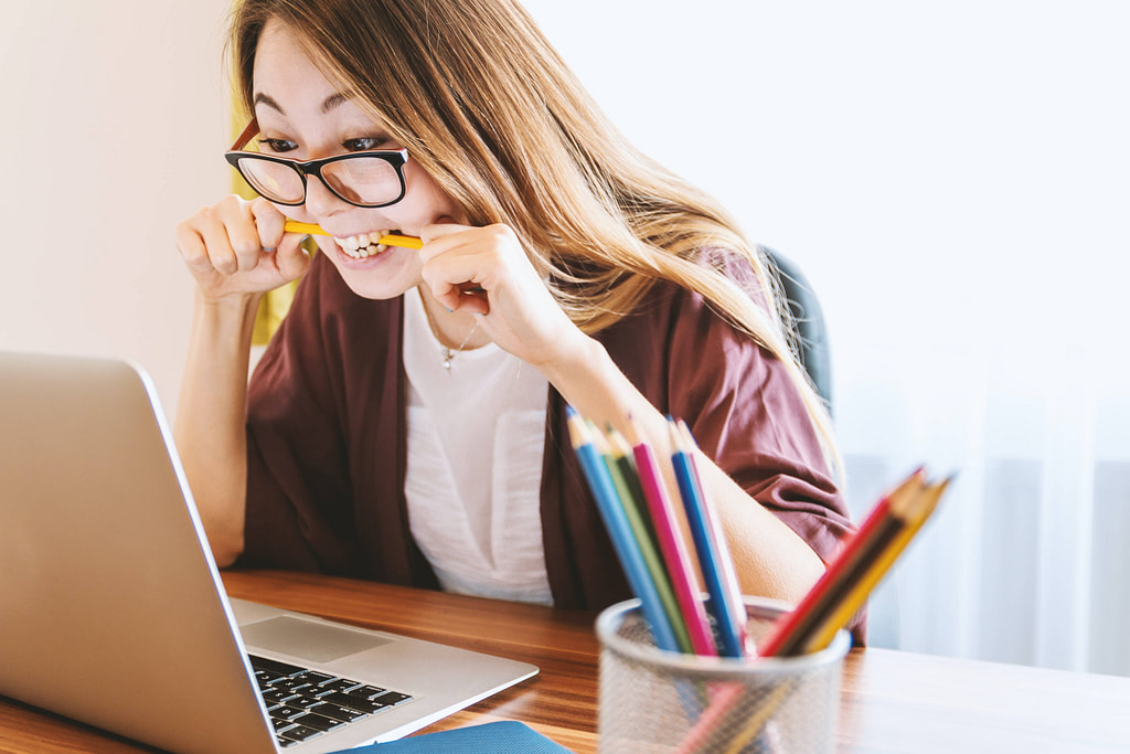 Woman wearing glasses biting on a pencil sitting in front of a laptop at desk